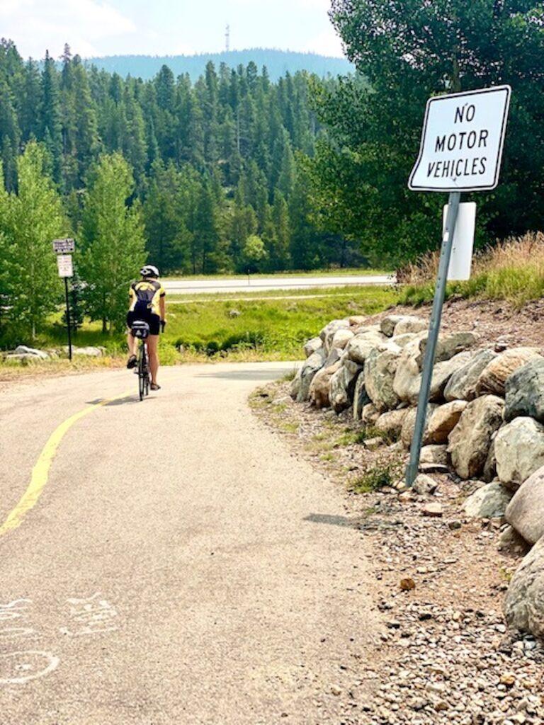 Cyclist rides her bike down a paved trail around Breckenridge.