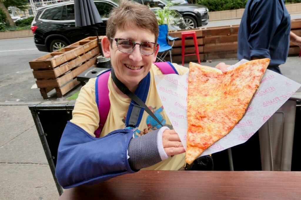 Sue Davies holding a jumbo slice from Koronet, larger then her head and part torso.