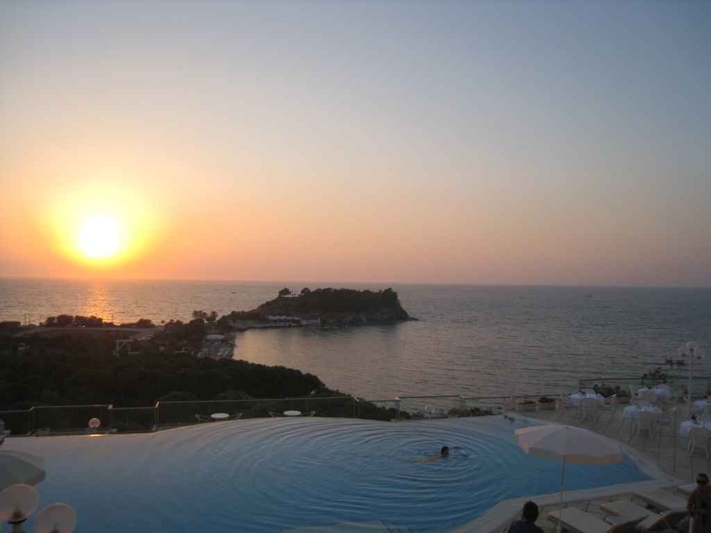 sunset seen from a boutique hotel Kuşadası, Turkey as a woman swims in the infinity pool