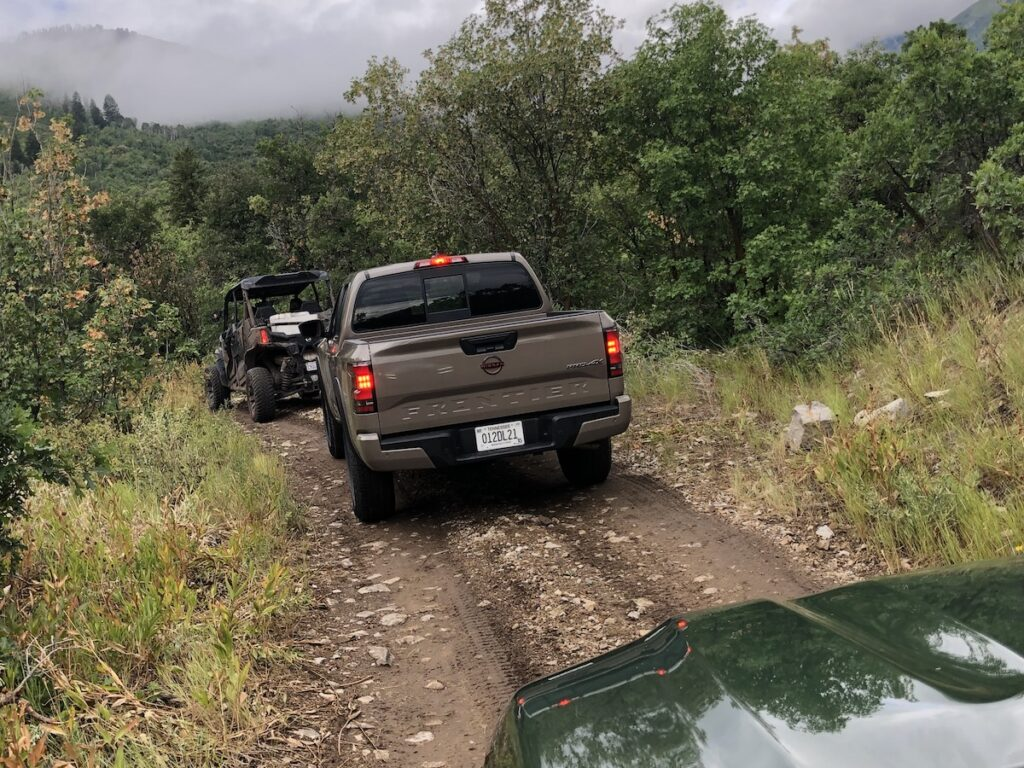 Trucks line up and enter the dirt off road trail.
