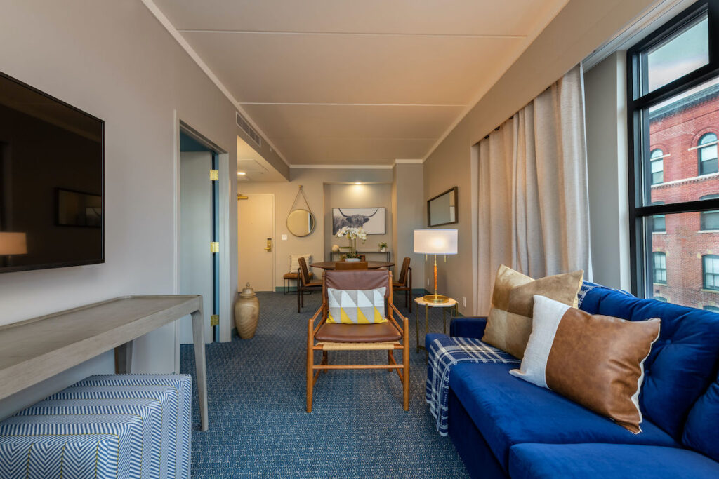 Vibrant blue couch and brown sleek leather chair in the living portion of the hotel suite.