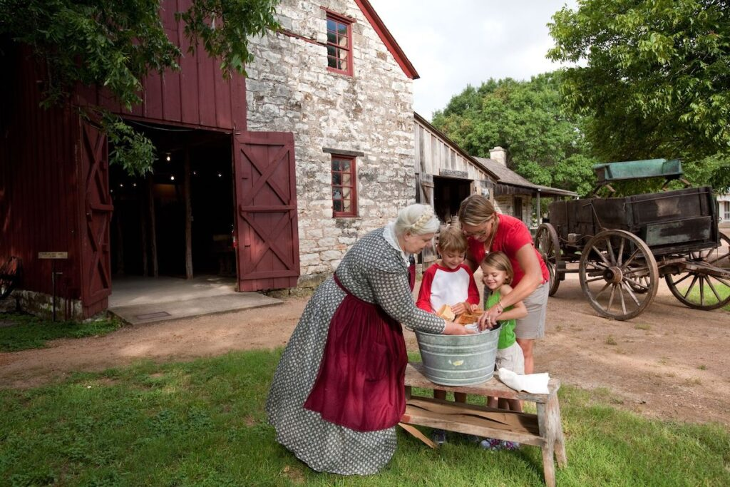 Senior woman shows childen how to wash clothes with a wash board outside at the Fredericksburg Pioneer Museum.