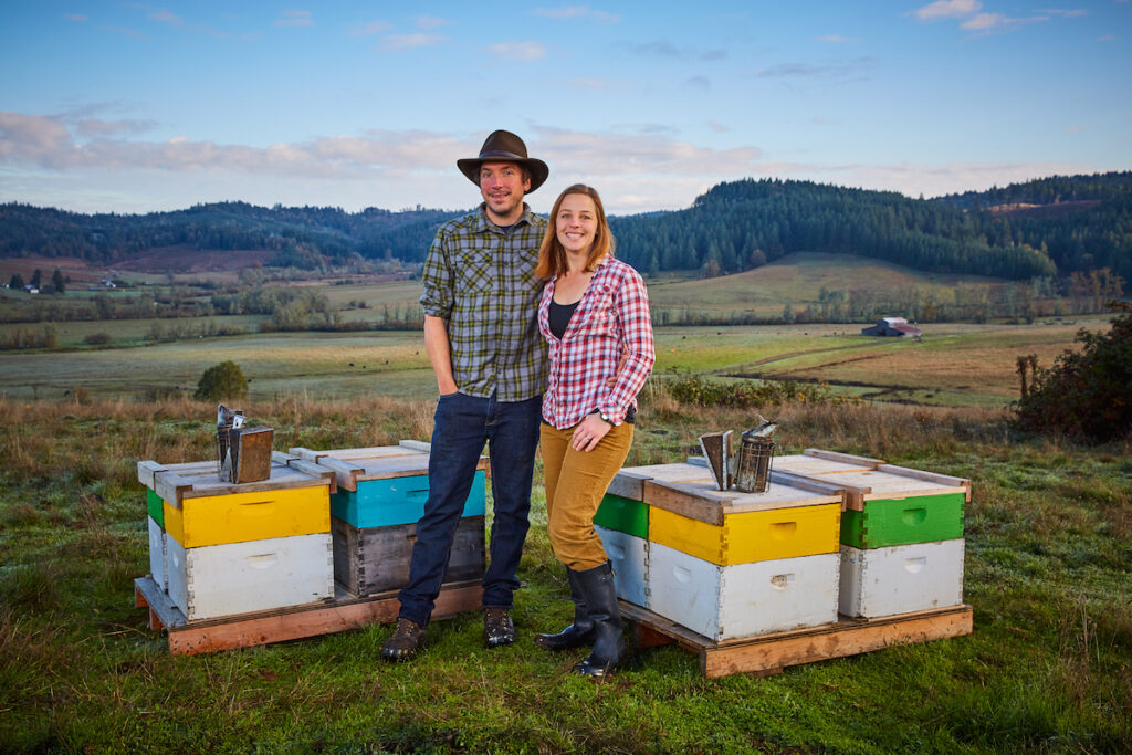 A man and woman stand together next to beehives at Queen's Bounty.