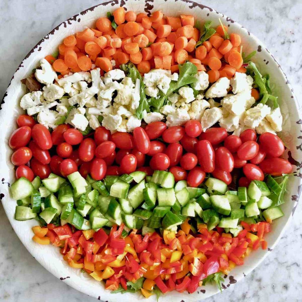 Colorful rainbow salad ingredients prepped for mason jar.