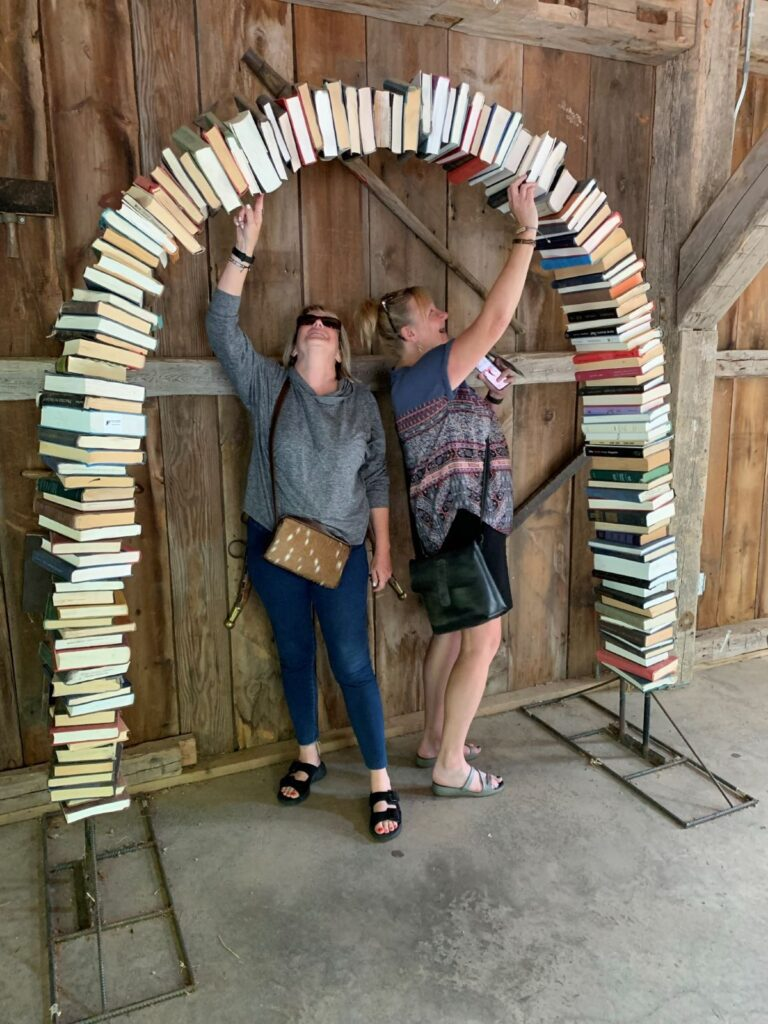 Two women hold up book arch at the Bookworm Gardens.
