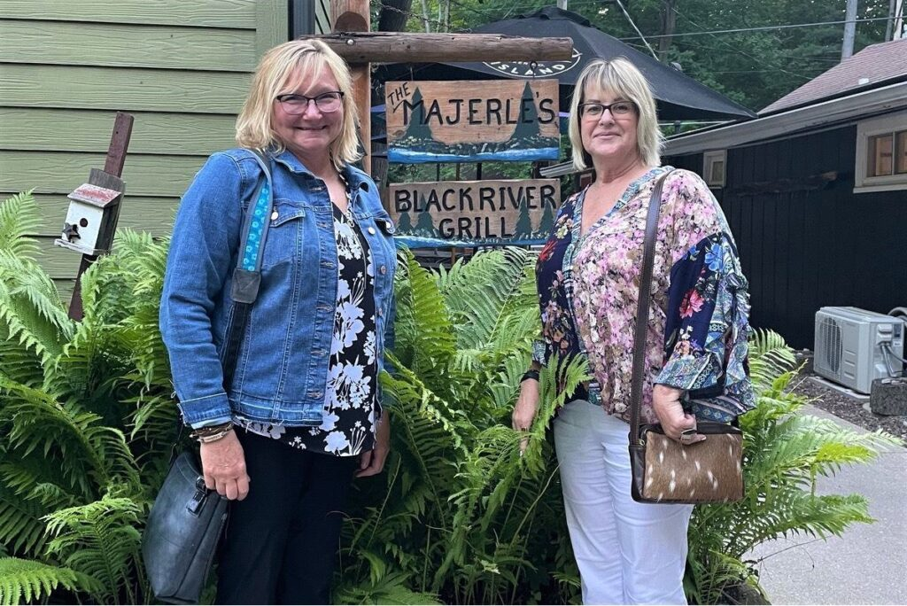 Two women stand at the entrance to Majerle's Black River Grill.