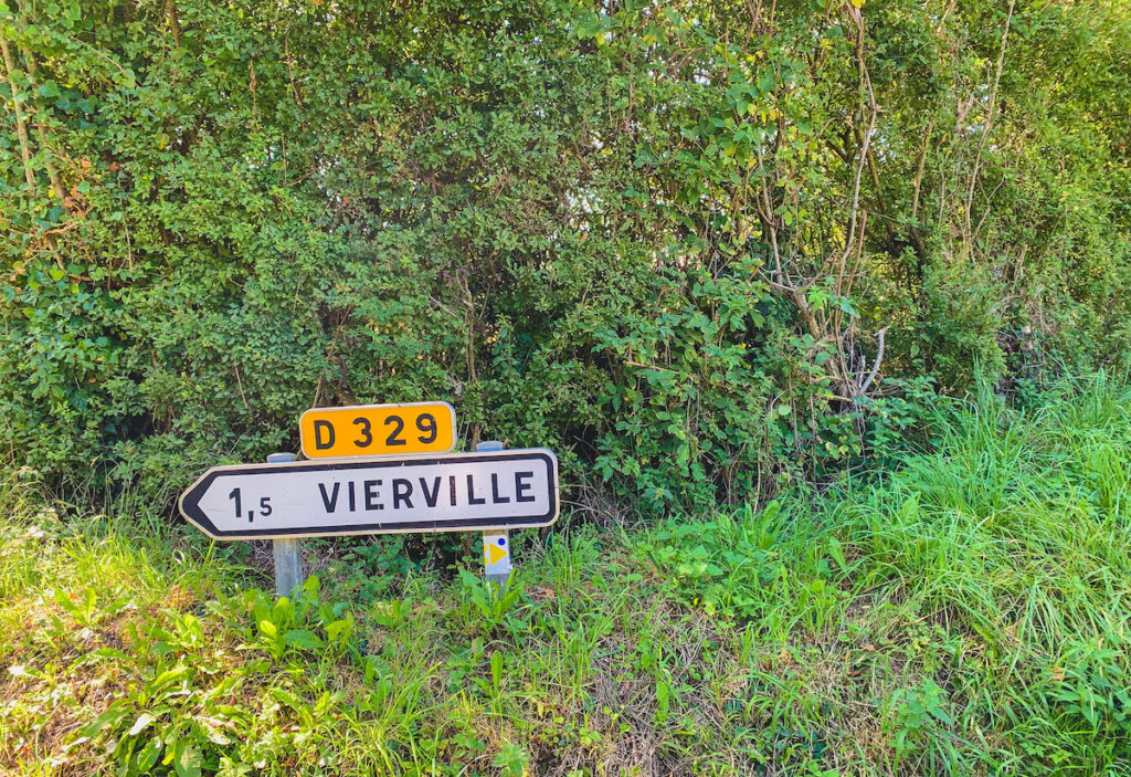 Very short white and yellow sign in Normandy Countryside.