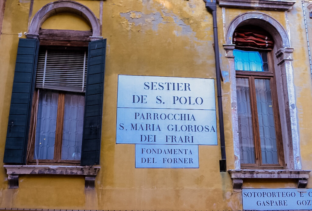 Street sign in Venice painted on a building.