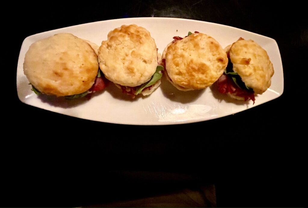 An appetizer of sweet potato biscuits filled with Edwards Surry ham, shallot marmalade and watercress.