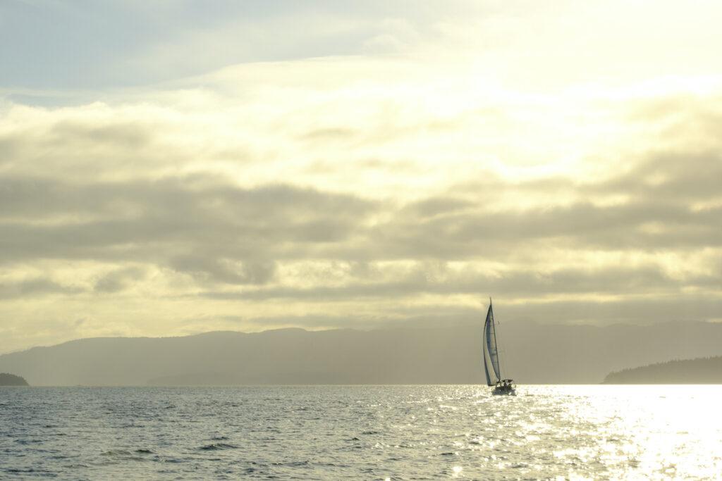 Sailboat sails across a glistening bay.