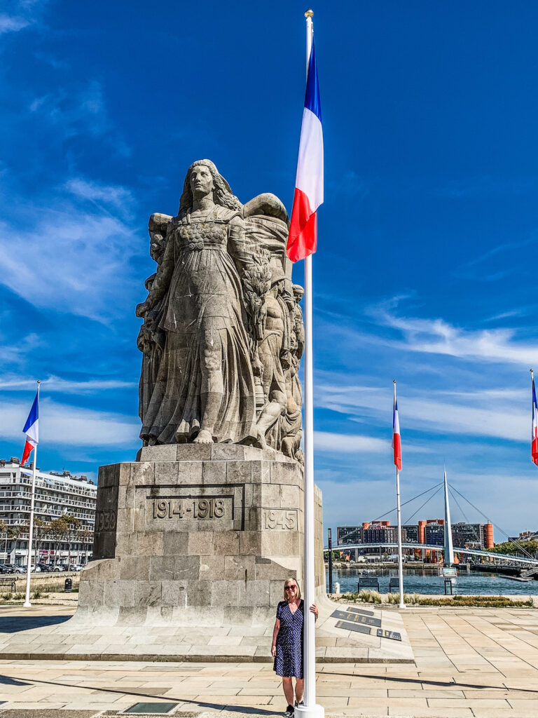 Woman stands in front of War Memorial in Le Havre.