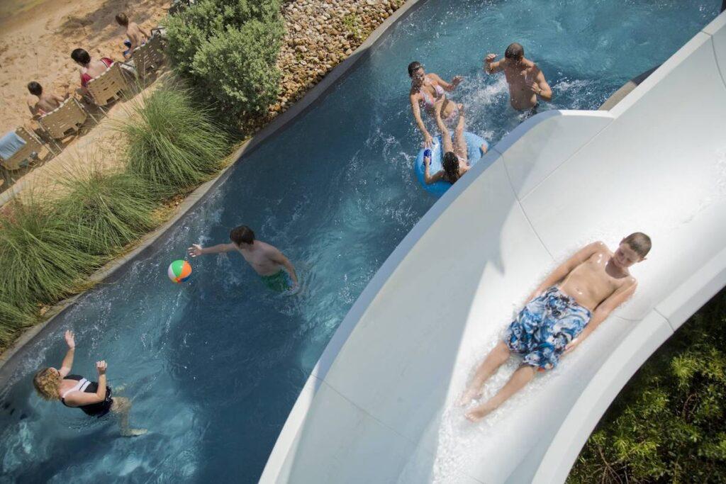 Families having fun at the water slide at Hyatt Regency Lost Pines Resort.