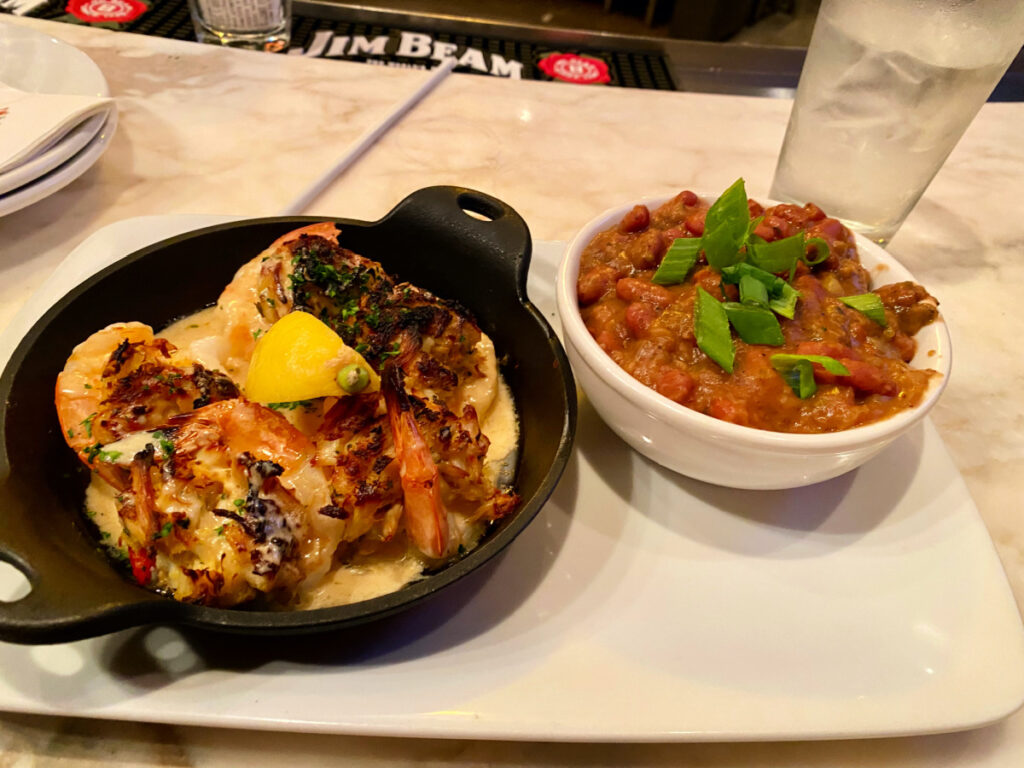 Harry's baked shrimp in cast iron skillet and bowl of beans.