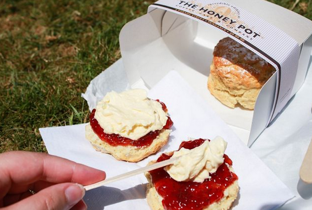"""""""Clotted cream"""" and local strawberry jelly being spread across a homemade vegan sweet scone."""