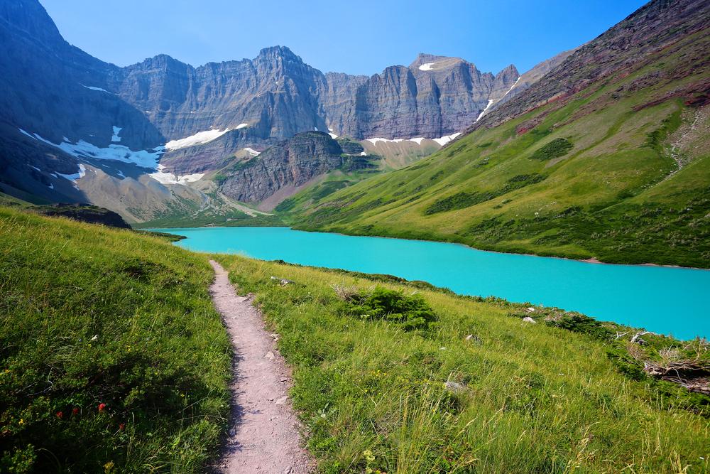 Hiking trail in beautiful alpine scenery to emerald green Cracker Lake in Glacier National Park