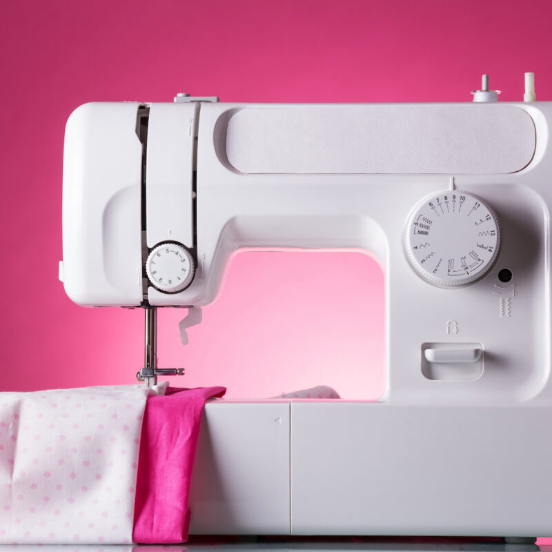 Multifunctional sewing machine, fabric under presser, on pink