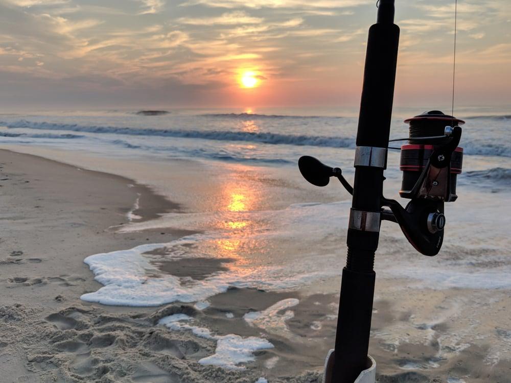 Surf fishing at Assateague Island sandy beach at ocean sunrise
