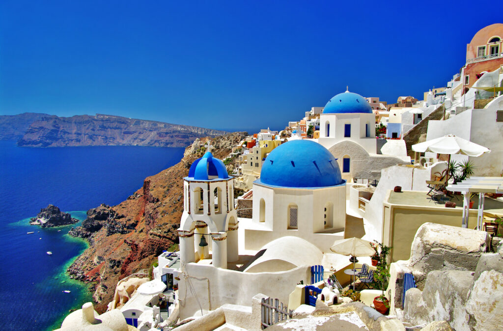 Cliffside with harbor and buildings in amazing Santorini with deep blue sky and water.