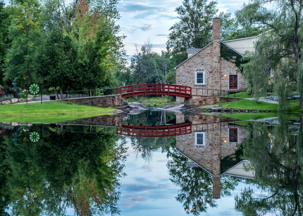 Red footbridge and old stone house surrounded by trees, reflected in the perfectly still pond in Perth, Ontario, Canada.