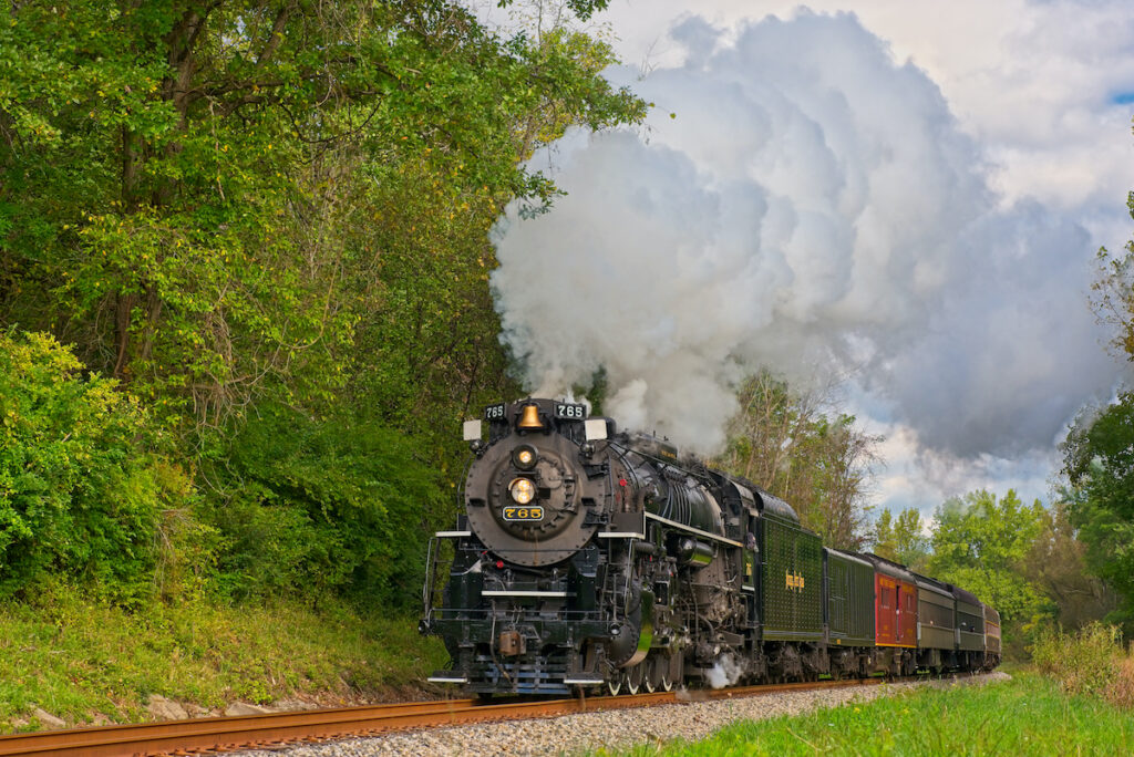The vintage Nickel Plate 765 steam locomotive pulls an excursion train of passenger cars on the Cuyahoga Valley Scenic Railroad south of Cleveland.