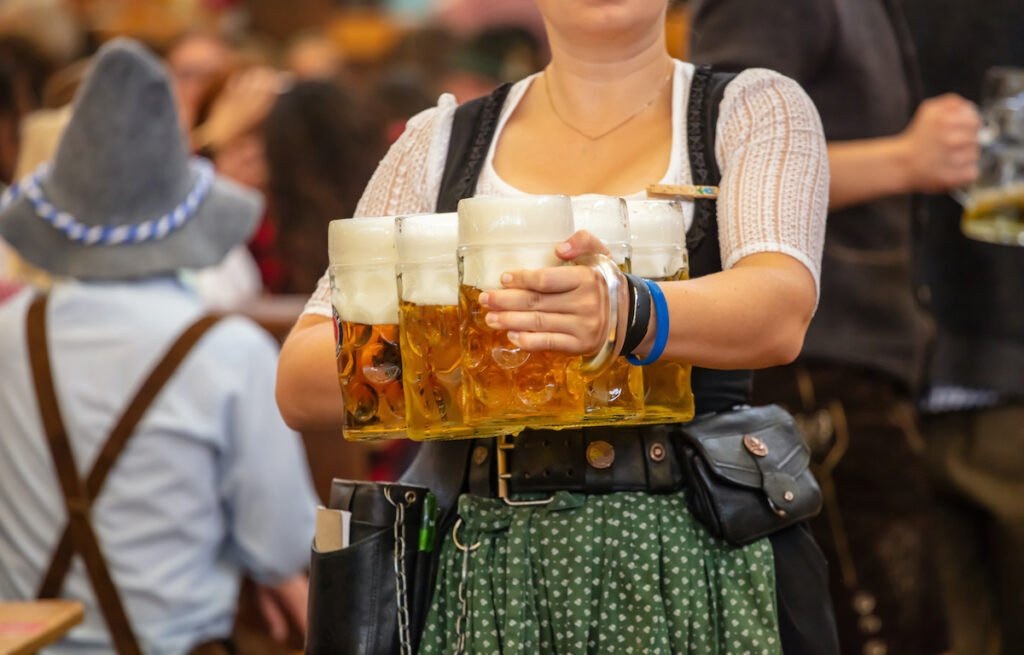 Oktoberfest, Munich, Germany. Woman waiter with traditional costume holding beers.