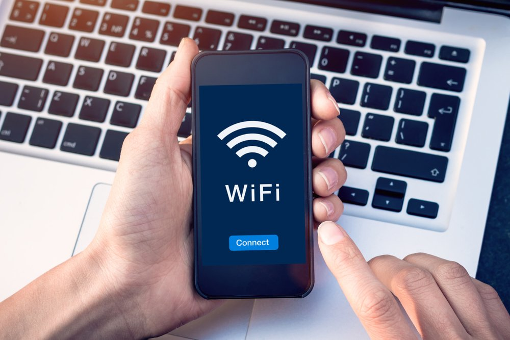 WiFi wireless internet network with smartphone at coffee shop or hotel with button on mobile device screen, free public hotspot secure access to web for email and website browsing