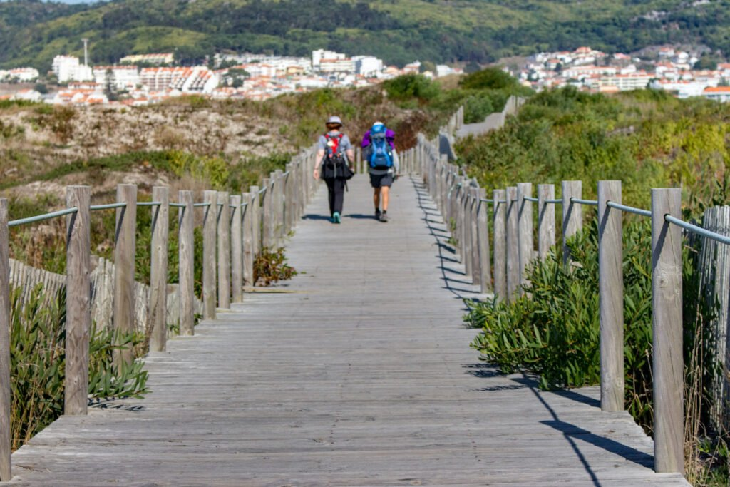 Couple of unknown pilgrims walk on  a wooden path down the Camino de Santiago trail.
