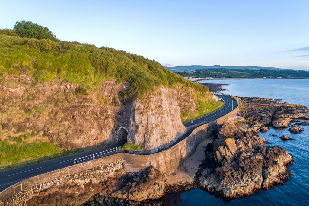 Black Arc tunnel and Giant's Causeway coastal road.  Scenic drive along the east coast of County Antrim, Northern Ireland, UK.