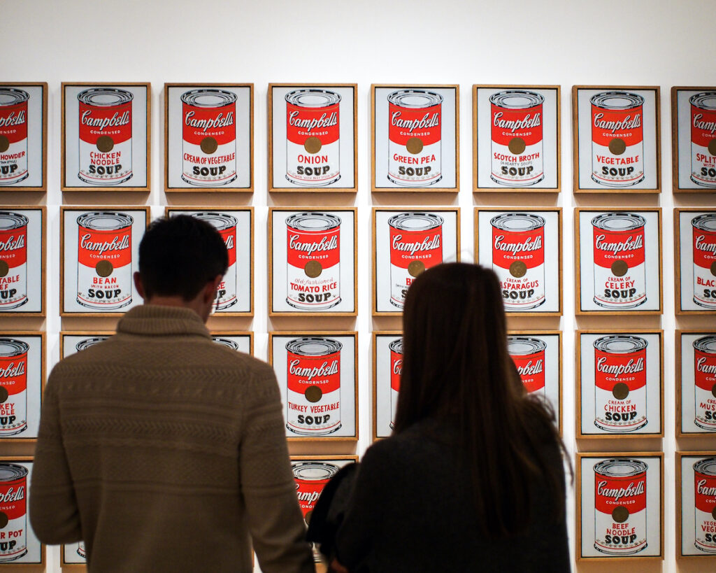 Young couple view Campbell's Soup Cans, the artwork by Andy Warhol at Museum of Modern Art, or MoMA, Manhattan, New York.