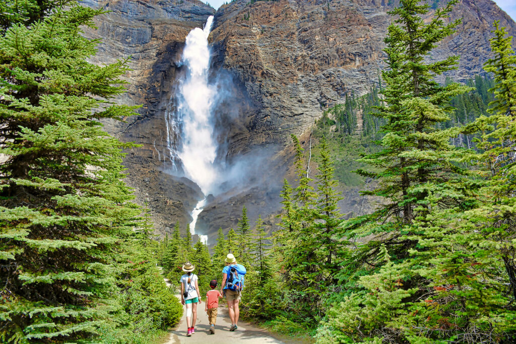 Family walks down trial to view Takakkaw Falls in the background at Yoho National Park, Canada.