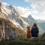 woman and dog sit looking out at mountains