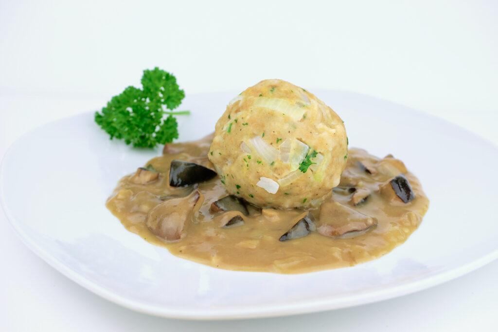 Homemade Bavarian bread dumpling, known in south Germany as Semmelknödel, on a wild mushroom, bay bolete, with cream gravy.