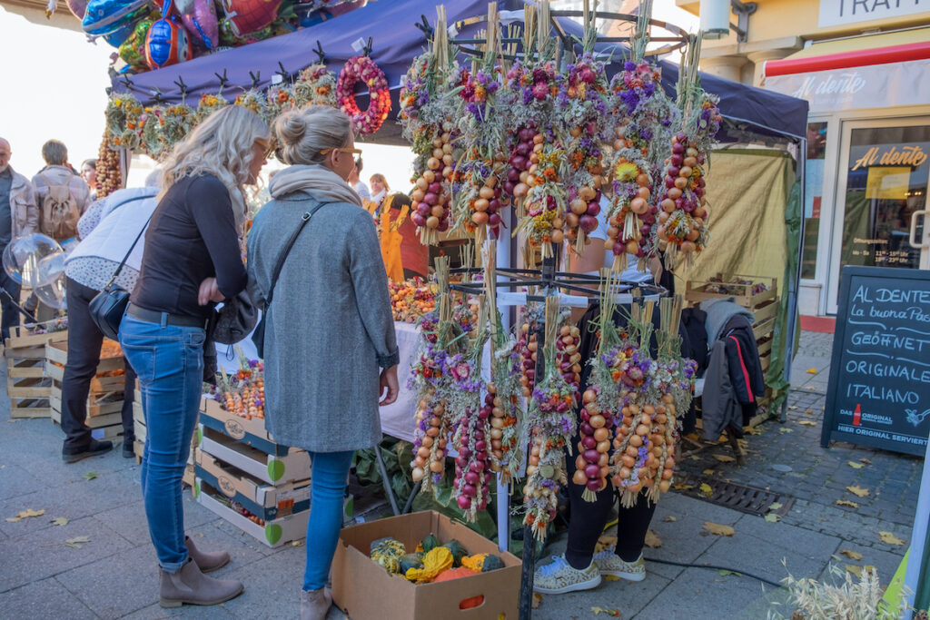 """The famous traditional October onion market """"Zwiebelmarkt"""" holiday in Germany with tourists stopping to look at boths."""