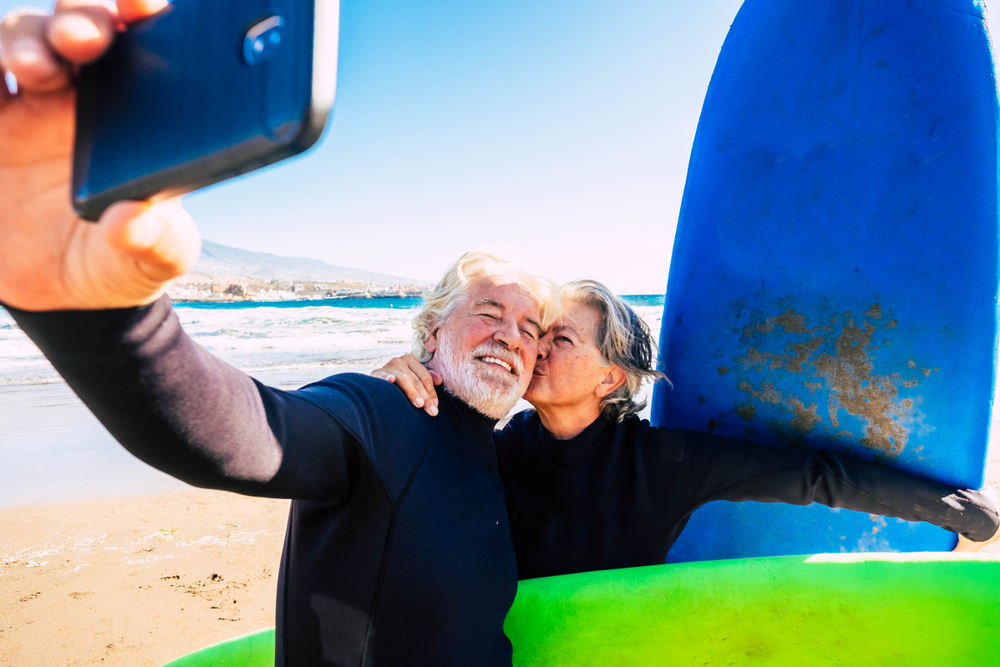 beautiful couple of two seniors at the beach with wetsuits and surfboard taking a selfie before go surf together - active mature people