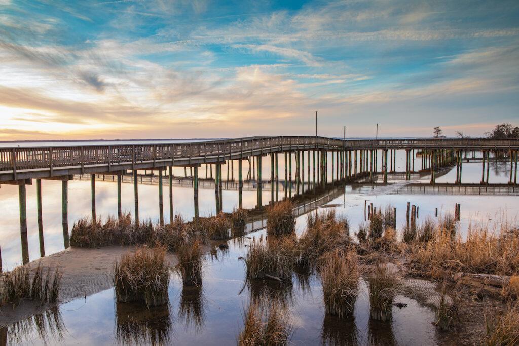 Soundside boardwalk over Currituck Sound in Duck, North Carolina on the Outer Banks during sunset.