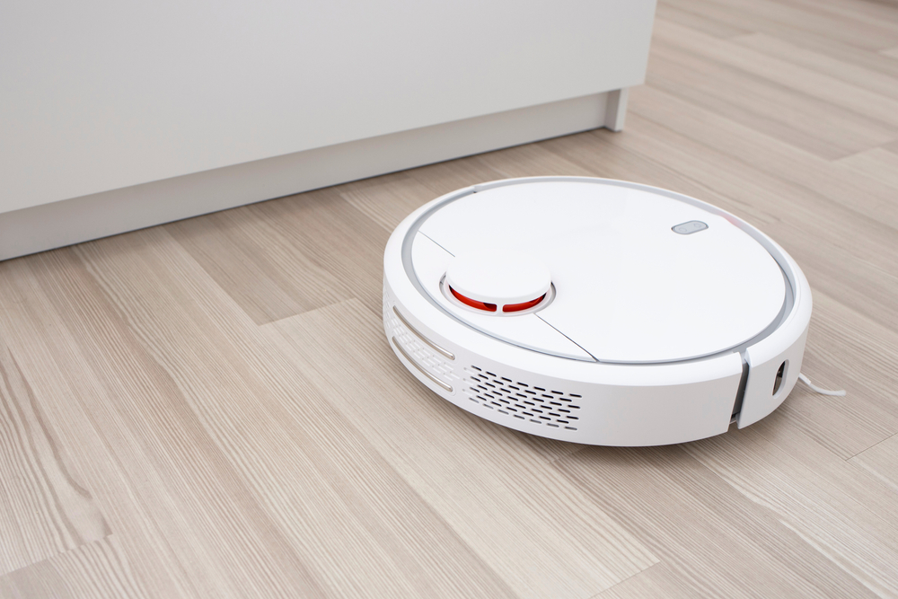 White robot vacuum cleaner on the floor in the living room