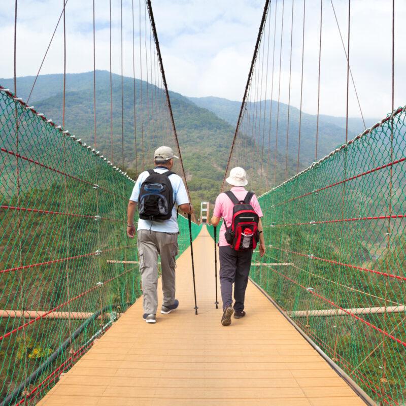 Mature couple hiking across a bridge.