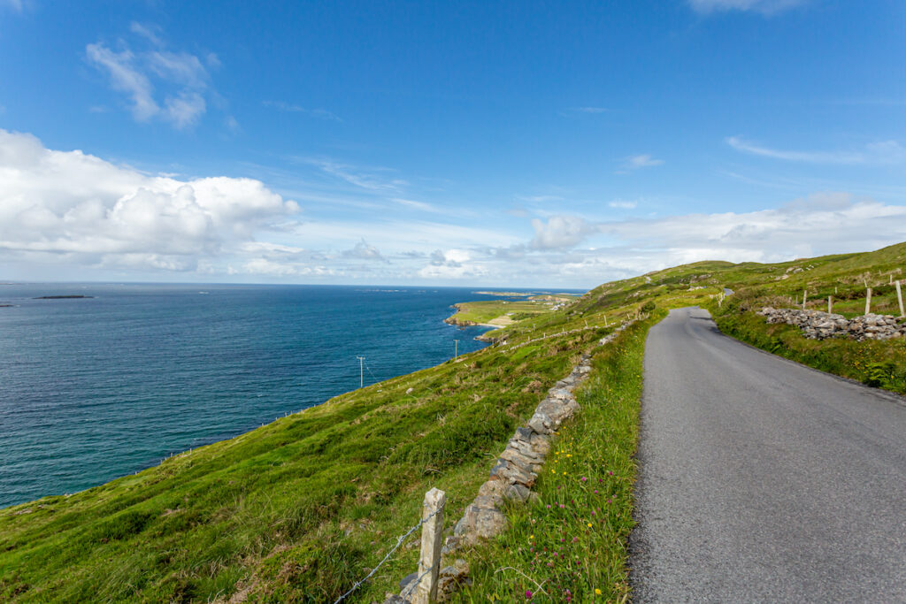 Sky Road with the most spectacular panoramic views over the Atlantic Ocean and the Connemara coastline, paved path between green grass and rocks.