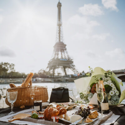 Picnic near the Seine in front of Eiffel tower. Fruits, french cheeses, shrimps, snacks, croissants, oysters, foie gras, delicacies, a bouquet of flowers and a bottle of expensive champagne.