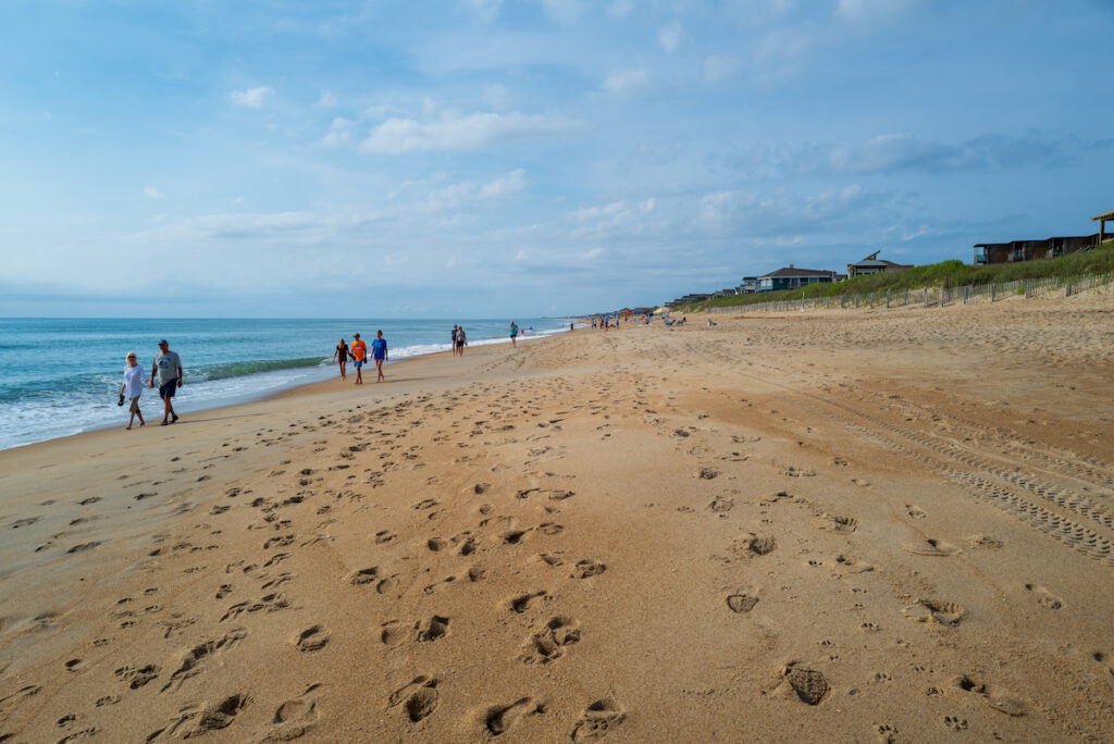 Visitors walk the beautiful morning beach in Duck, NC looking for shells and enjoying the beach.