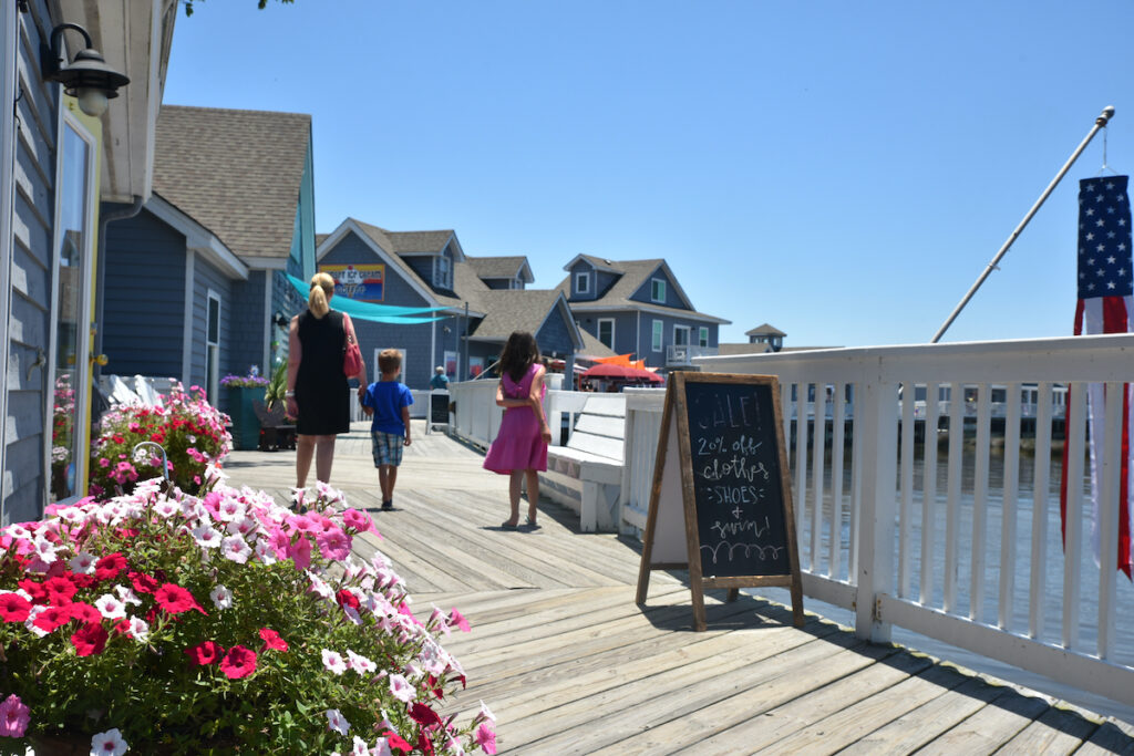 Tourists explore the waterfront shops on the boardwalk of Duck, North Carolina during summertime.