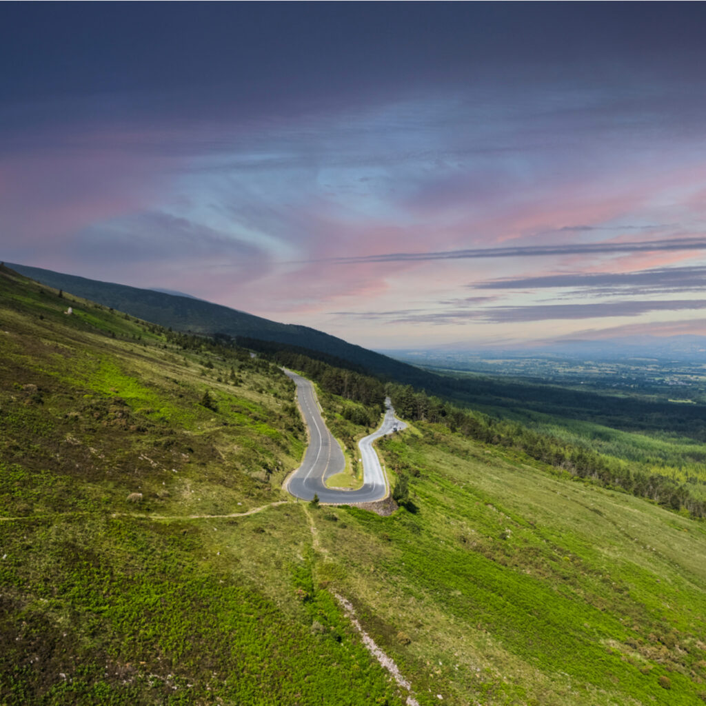 The Vee in Waterford and Tipperary, winding road in the Knockmealdown Mountains with purple sky and deep green hillside.