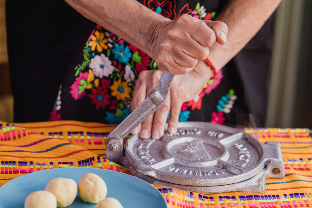mexican tortillas handmade: woman with traditional clothes pressing tortilla press in Mexico