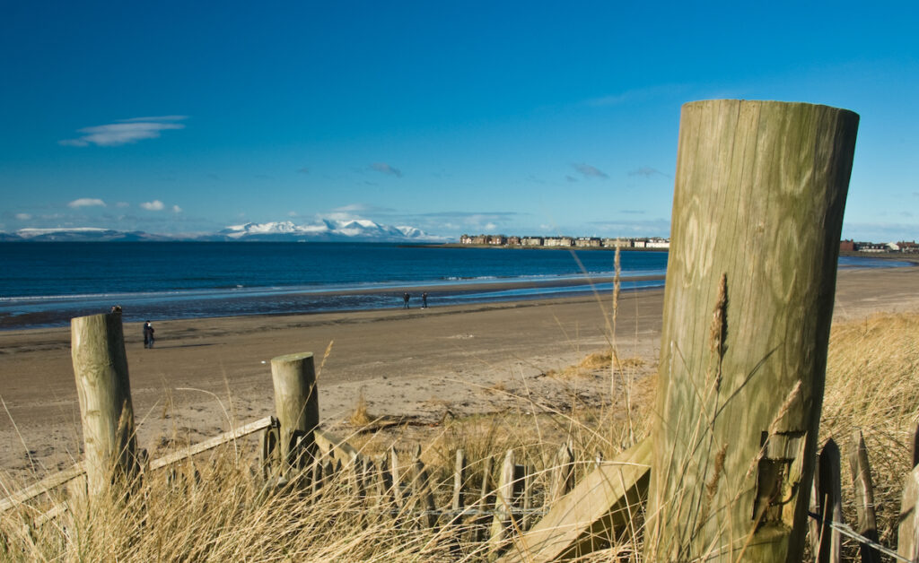 Snow-capped mountains on Island of Arran viewed from Troon beach, Ayrshire, Scotland, UK.