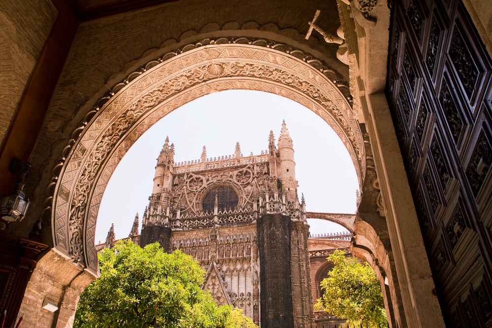 tower of the giralda seen by the garden of the orange tree of the cathedral of seville