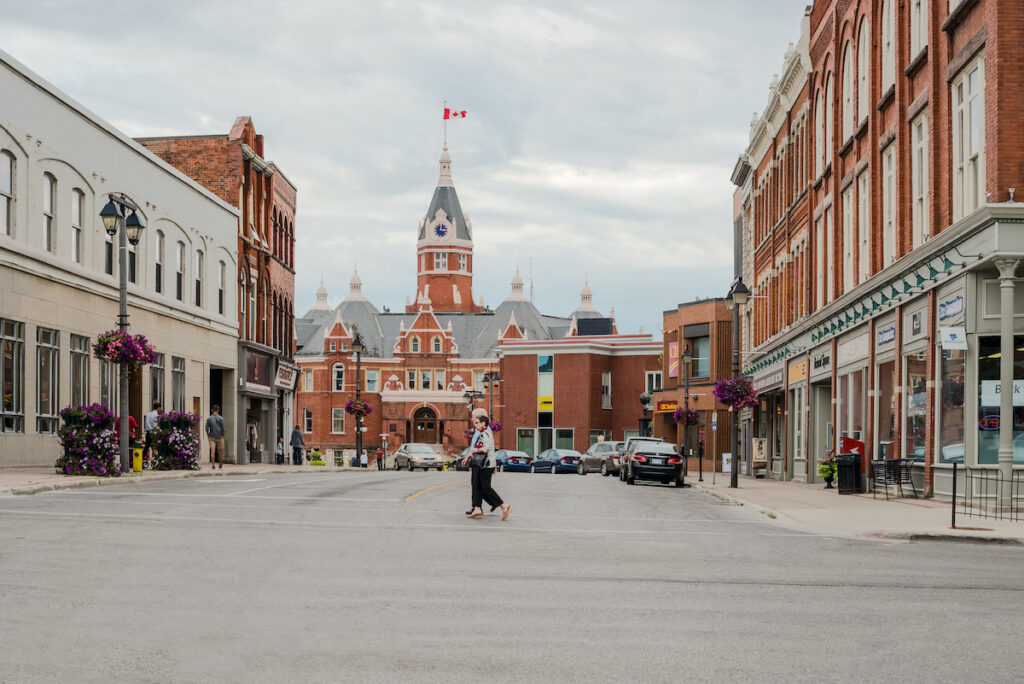 People crossing the street and the town hall building in the city of Stratford in Ontario at the background.