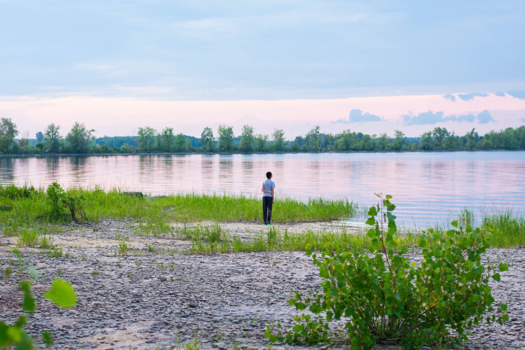 Boy looking at the sunset at Shirley's Bay in Ottawa, Ontario.