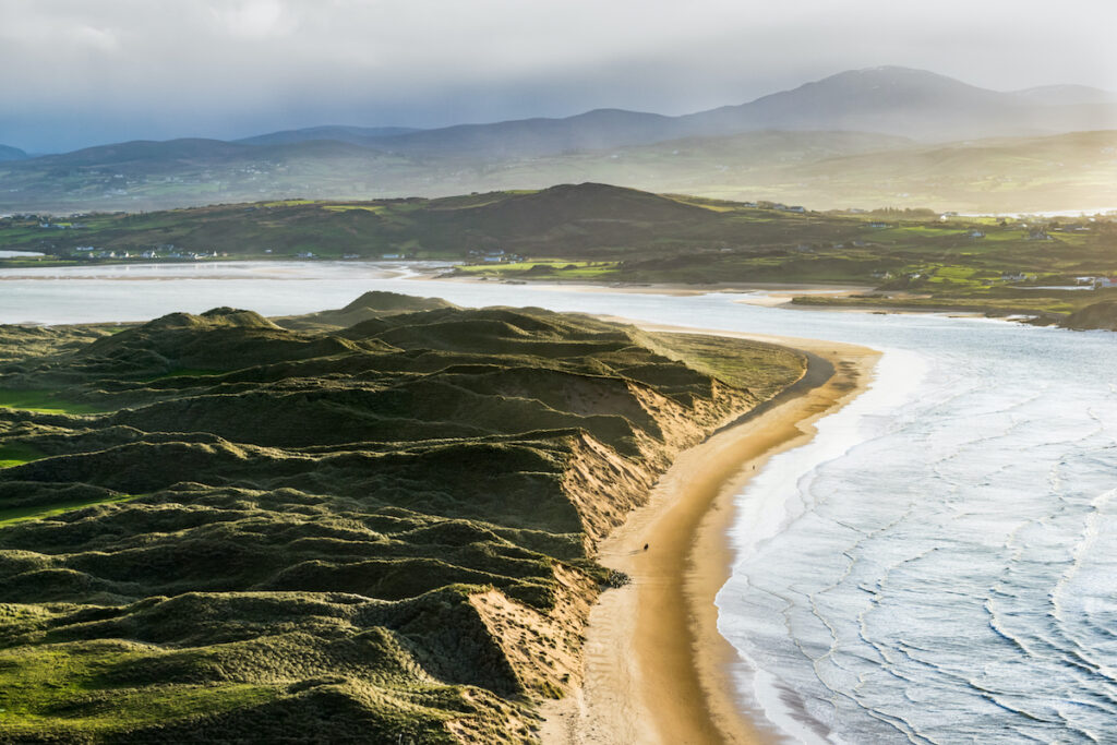 Beach and verdant jagged hills called Five Finger Strand on the Inishowen Peninsula in Donegal, Ireland.