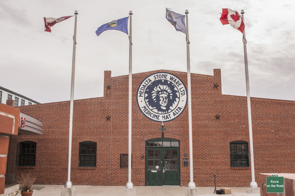 Medalta Stone Ware building and sign with four flag poles in front of the building.
