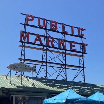 Public Market neon sign with smaller fish shaped sign underneath.